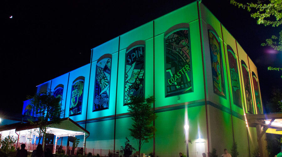 Laff Trakk Coaster Exterior at Night with Blue and Green lights illuminating the sides