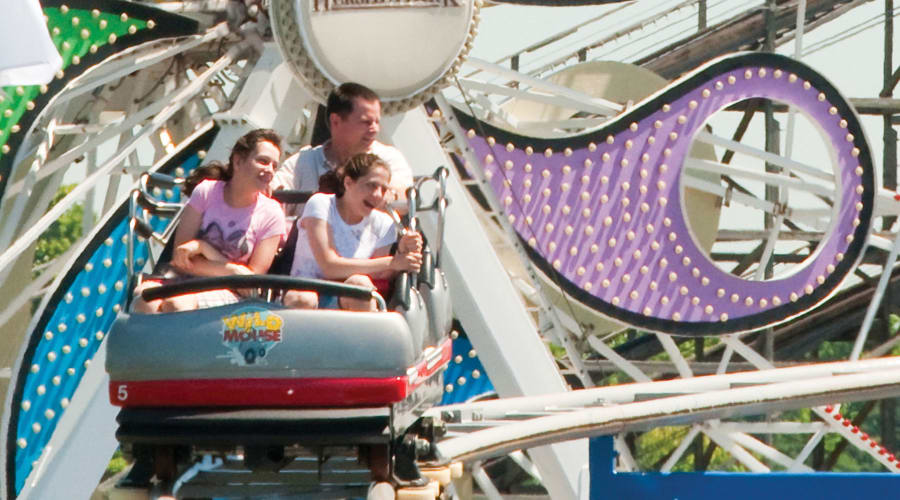 Family Riding Wild Mouse Coaster with the Ferris Wheel in background
