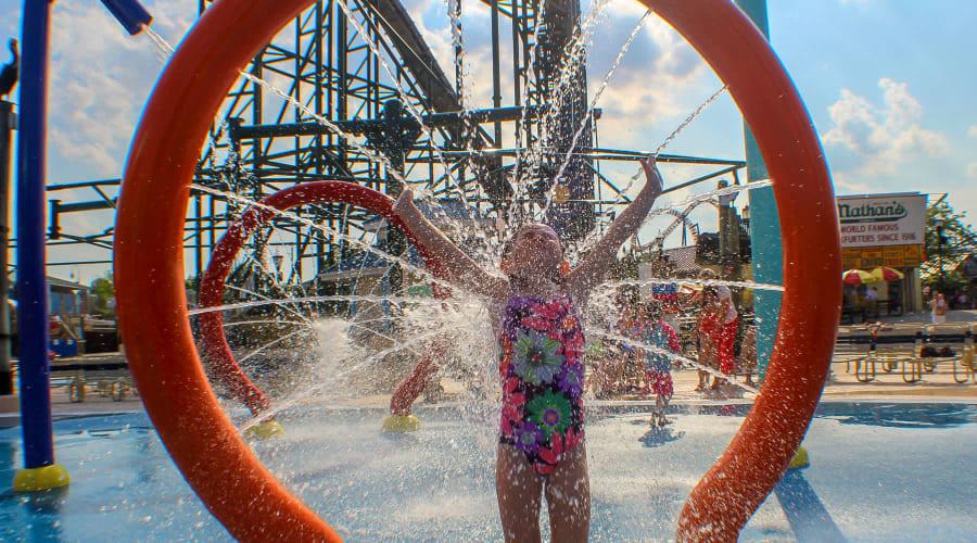 girl getting splashed at shoreline sprayground water attraction