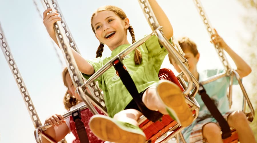 Girl with Braces and Pigtails Smiling on the Wave Swinger Ride